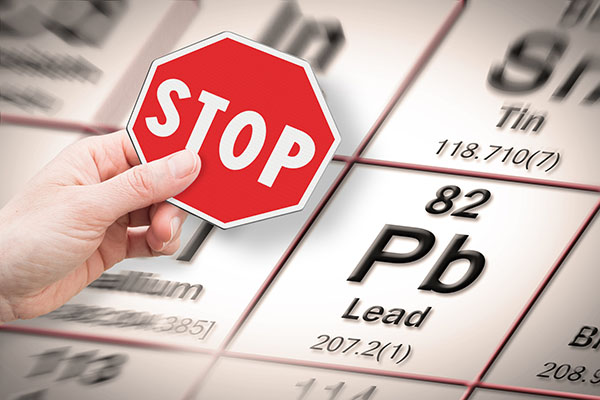Image of hand holding stop sign over lead on periodic table
